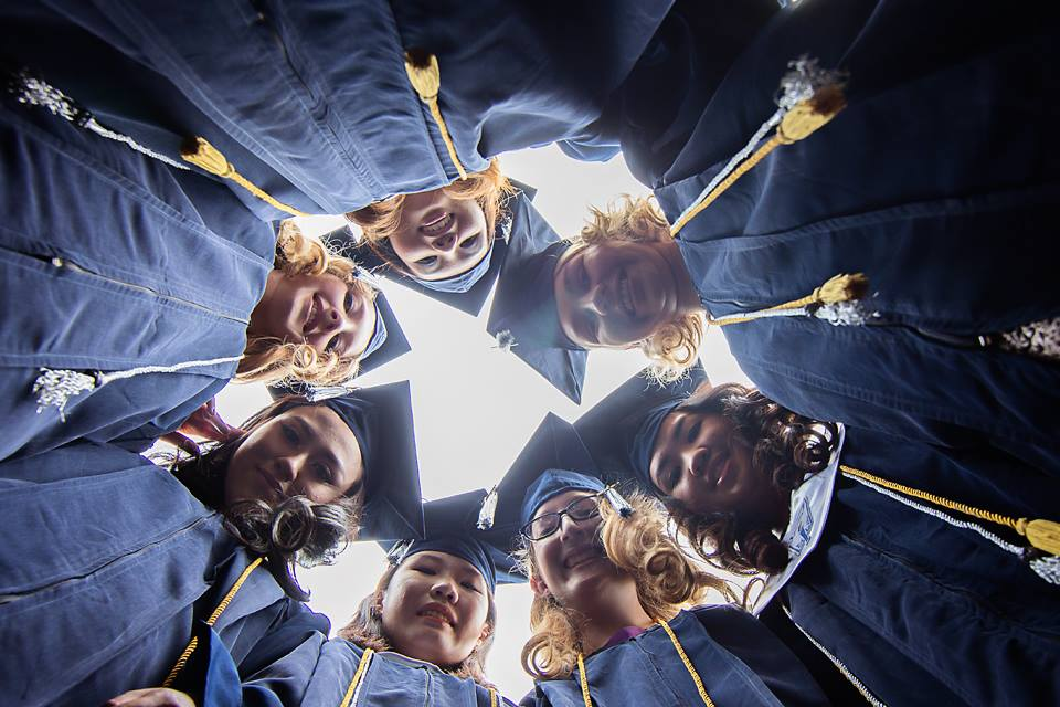 Image of a group of graduates looking down at the camera together before going to college