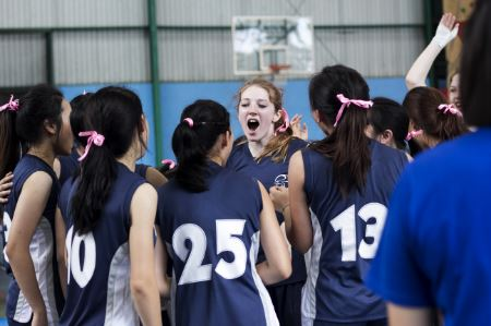 Image of a girl's basketball team playing in the gym