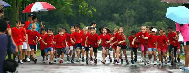 Image of happy students running in the rain