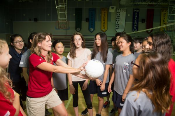 Image of a coach explaining volleyball to a group of students in the gym